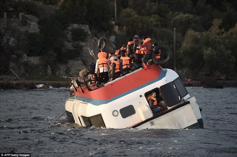 Sinking ship: An overcrowded refugee boat begins to sink off the Greek island of Lesbos after crossing the Aegean Sea from Turkey