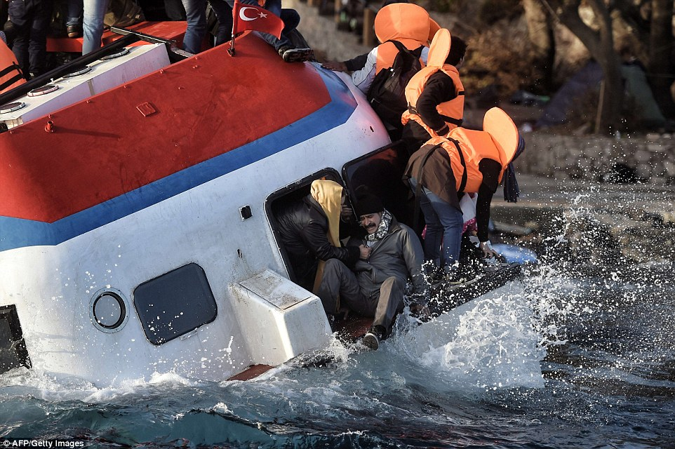 Despair: One man struggles to stay on board the boat as the rough seas force the passengers to take evasive action
