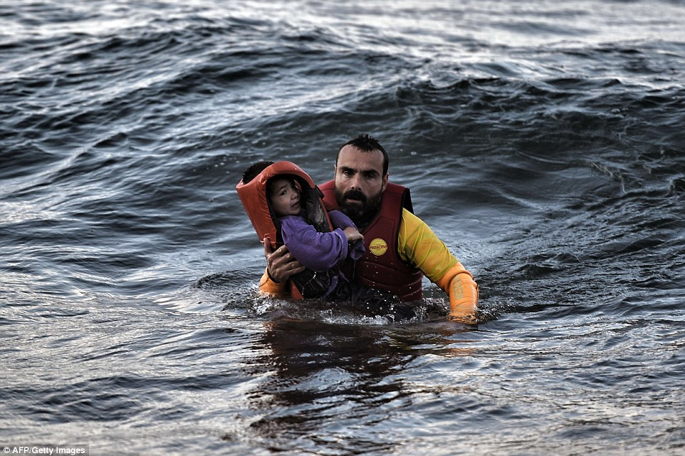 Saviour: A lifeguard rescues a child as a boat with refugees and migrants sunk, while crossing the Aegean sea from Turkey to the Greek island of Lesbos