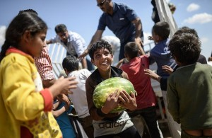 "A Syrian child holds a watermelon after they were distibuted near the Akcakale crossing gate between Turkey and Syria at Akcakale in Sanliurfa province on June 16, 2015.  Some 23,000 people have fled from Syria to Turkey between June 3 and 15, the UN refugee agency said. ""New fighting in northern Syria has seen 23,135 refugees fleeing across the border into Turkey's Sanliurfa province,"" during that period, spokesman William Spindler said, citing figures given by Turkish authorities.  AFP PHOTO / BULENT KILIC        (Photo credit should read BULENT KILIC/AFP/Getty Images)"