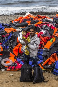 A man from Syrian town Aleppo poses with his child in front of a mound of life jackets as he arrive with other refugees on the shores of the Greek island of Lesbos after crossing the Aegean sea from Turkey on an inflatable boat on October 2, 2015 near village of Skala Sikaminias, Greece. Despite bad weather due to the upcoming Autumn, migrants and refugees are risking their lives in search of a better one in the European Union. Officals have warned that a rise in migrant deaths is expected as weather conditions gradually worsen.  (Photo by Matej Divizna/Getty Images)