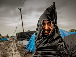 "A migrant, who protects himself from the rain with a plastic trash bag, walks through a mudpath of the ""New Jungle"" migrant camp in Calais, where thousands of migrants live in the hope of crossing the Channel to Britain, on October 21, 2015. European Commission chief Jean-Claude Juncker has called a mini-summit in Brussels on October 25 to tackle the migrant crisis along the western Balkans route, his office said. AFP PHOTO / PHILIPPE HUGUEN        (Photo credit should read PHILIPPE HUGUEN/AFP/Getty Images)"