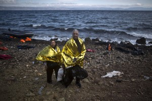 "In this photo taken on Friday, Oct. 2, 2015, Syrian refugee Ali Shaheen, 62, and his wife Abeer, 52, who came from the countryside of Damascus, Syria, pose for a picture shortly after arriving on a dinghy from the Turkish coast to the northeastern Greek island of Lesbos. ""Me and my wife are old and we can't walk, we were mistreated in Turkey, we are so tired,"" Ali said. (AP Photo/Muhammed Muheisen)"