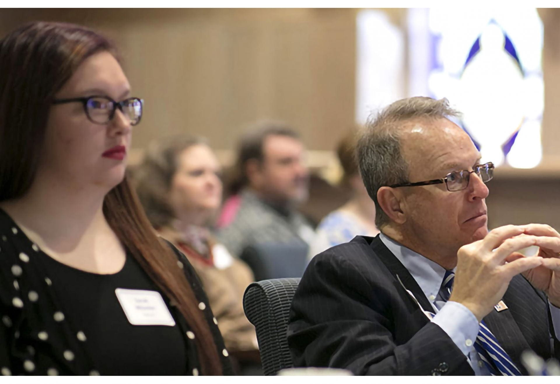 There are two individuals sitting at a table very attentive to an ongoing showcase.