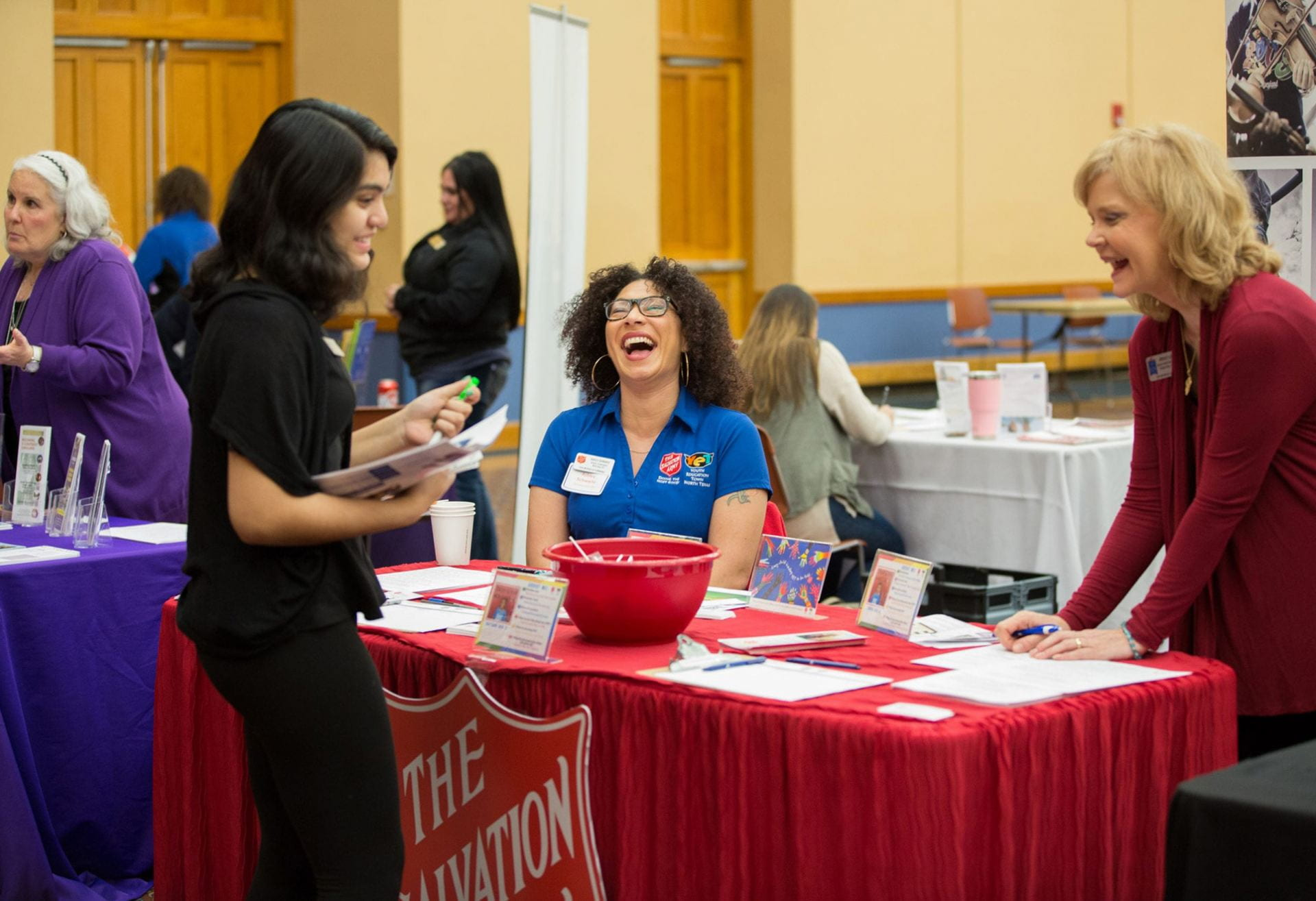 Three event attendees share a laugh as they discuss the company they represent.