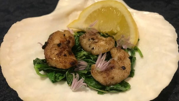 3 walleye cheeks on a bed of sauteed greens with a lemon wedge