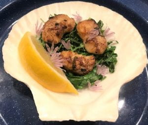 walleye cheeks served on sauteed greens in a scallop shell