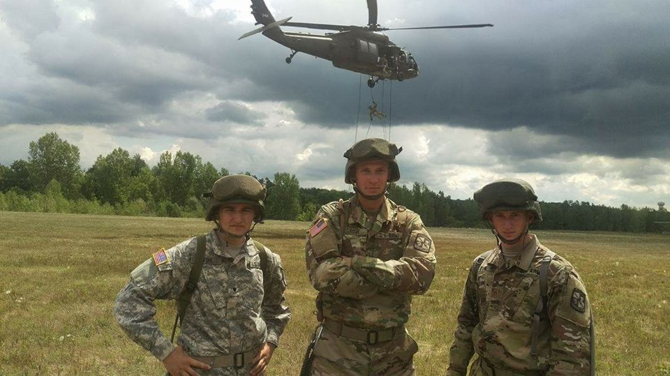 Three Excelsior Battalion members pose in front of a UH-60 Blackhawk as a stick of air assault candidates rappel from the helicopter.
