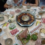 Hot pot in center of the table over an open flame. Bottom centered are the duck intestine.