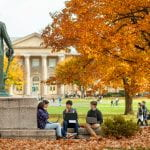 Students sit on the Arts Quad in fall.