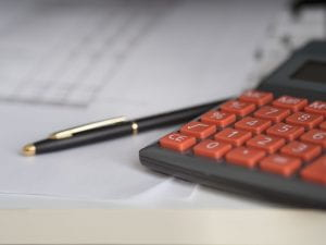 A calculator and pen on a table.