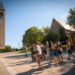 Prospective students walk across Ho Plaza towards McGraw Tower