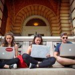 Three students sit outside with their laptops.