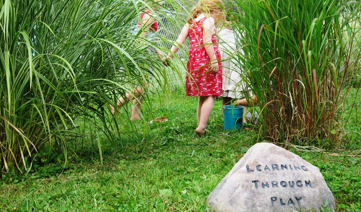 Children playing in tall grasses near a stone engraved with Learning Through Play