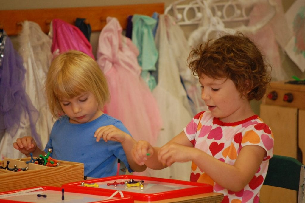 Two girls play with a magnetic manipulative toy