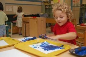 Boy fingerpaints with blue paint
