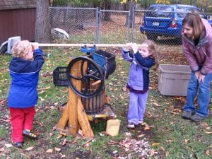 Two children press apple cider while a teacher looks on