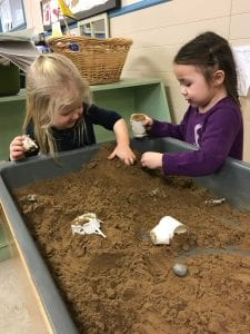 Two girls play at sensory table filled with sand.