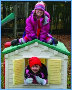 Two children play outside in a playhouse