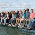 Clark lab members sitting along the dock on Skaneateles Lake during retreat 2018