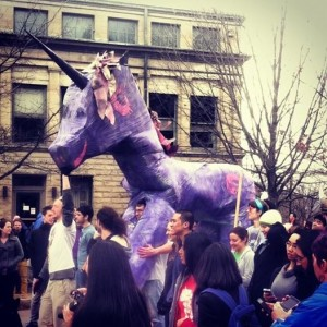The physicists triumphantly march their unicorn in the parade.