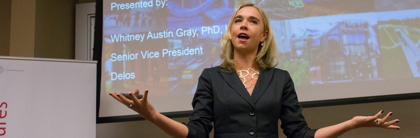 Photo of Whitney Austin Gray, Senior Vice President at Delos, giving a lecture