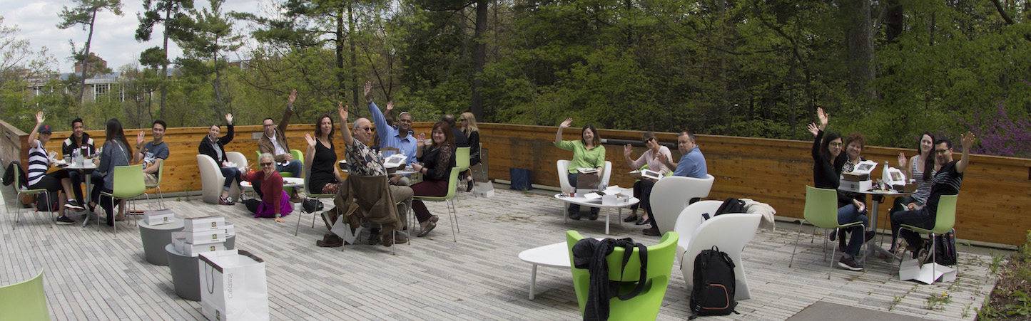 Photo of CIHF staff and affiliates sitting at modernist tables next to a forest