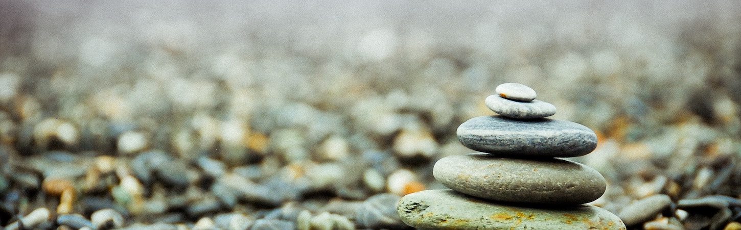 Photo of a stack of rocks from biggest on the bottom to smallest on the top, in a field of pebbles