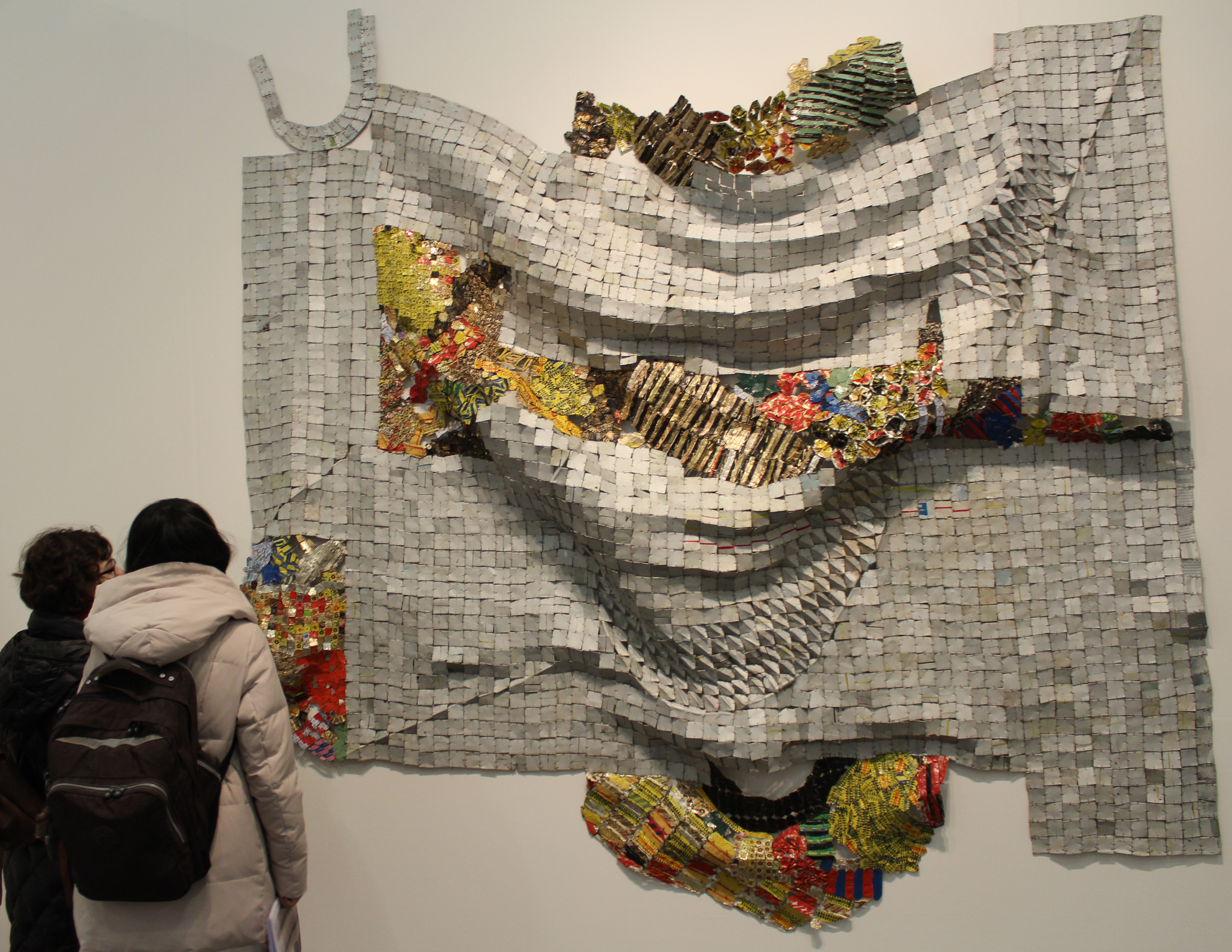 Pauline Shongov (B.F.A., left) and Yuxi Xiao (B.F.A., right) looking at a piece by artist El Anatsui.