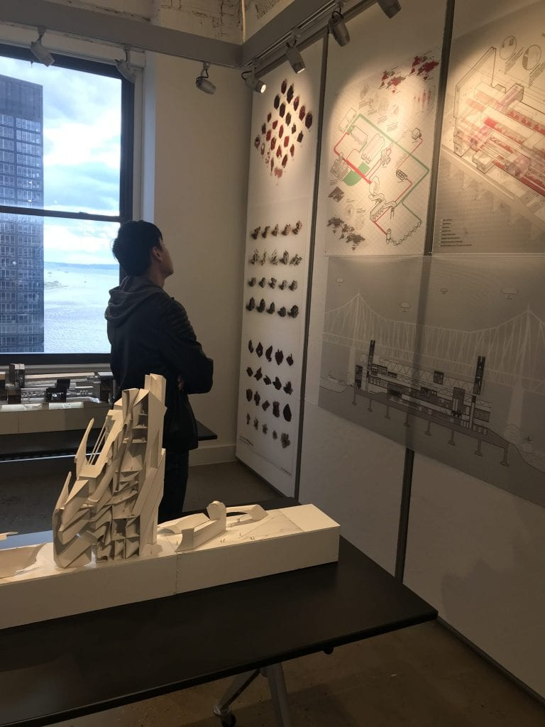 Person looking at three panels depicting architectural drawings.