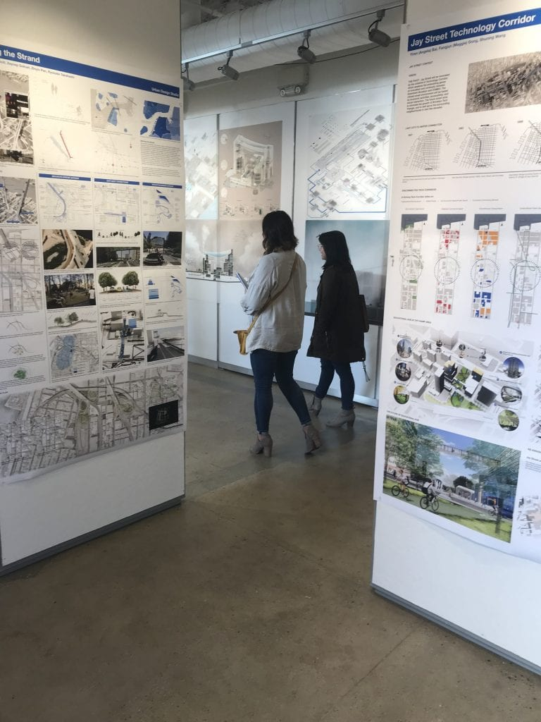 Individuals walking between panels showing architectural drawings.