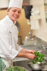 Culinary Immersion student in chef's whites sorts herbs into a colander
