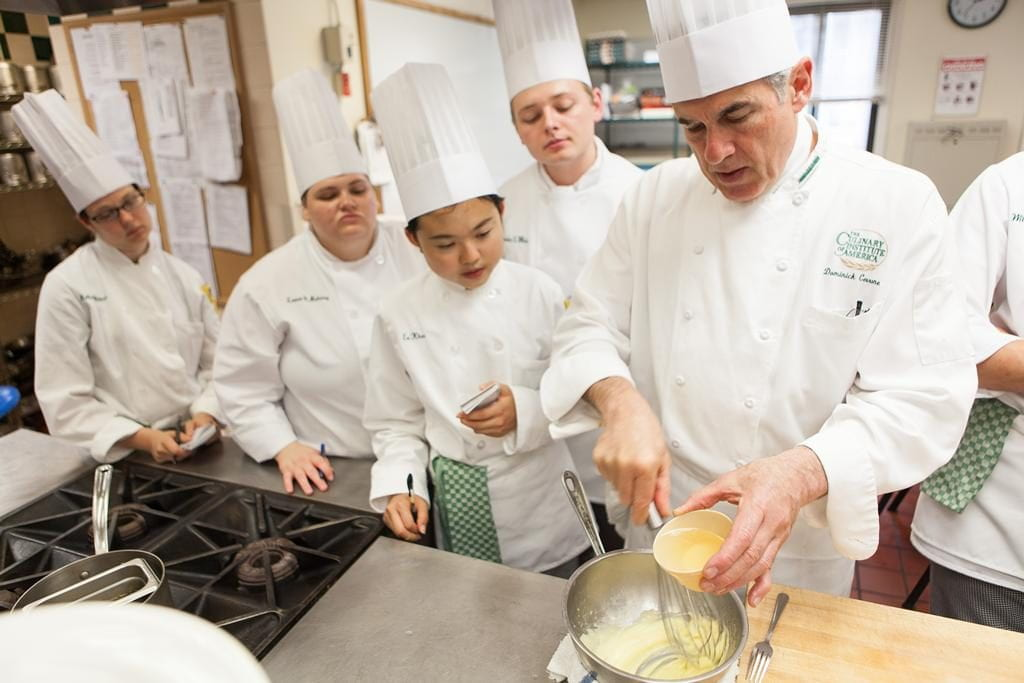 Chef Cerrone whisks egg into a mixture while five students in chef jackets observe in teh Culinary Immersion class.