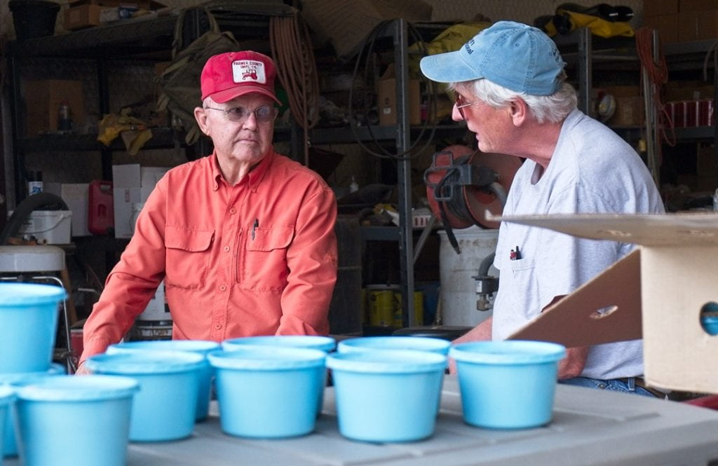 Cornell University Entomologist Elson Shields, right, talks with farmer Gary Frost as cups filled with biocontrol nematodes from New York State await application on Frost's farm in Dalhart, TX.