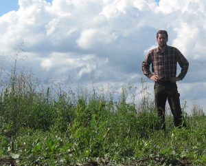 Bryan Brown, Ph.D. stands in an unplanted cornfield where weeds have gone unmanaged