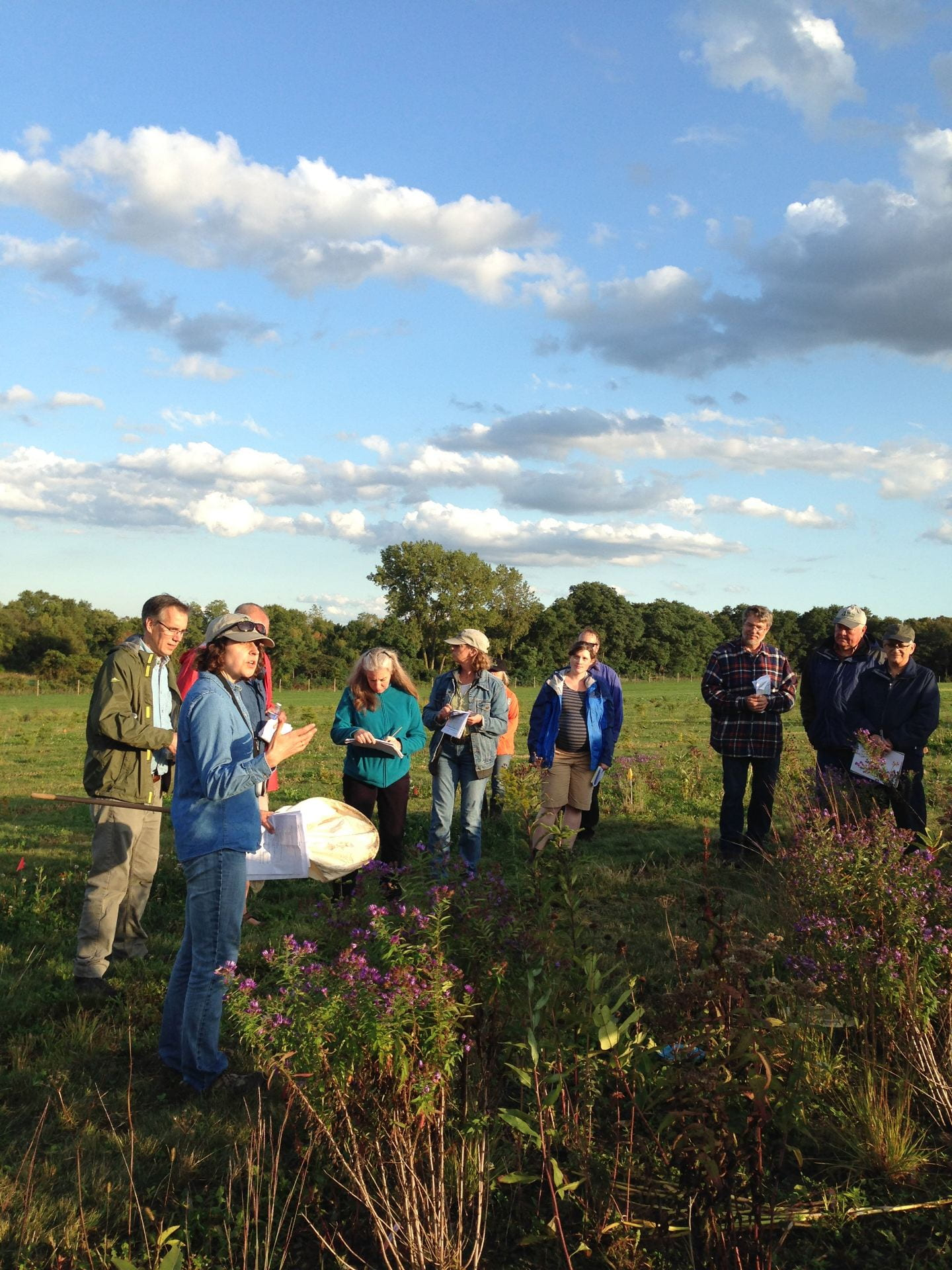 photo shows six guests and two speakers from the IPM program standing near one of the habitat plots
