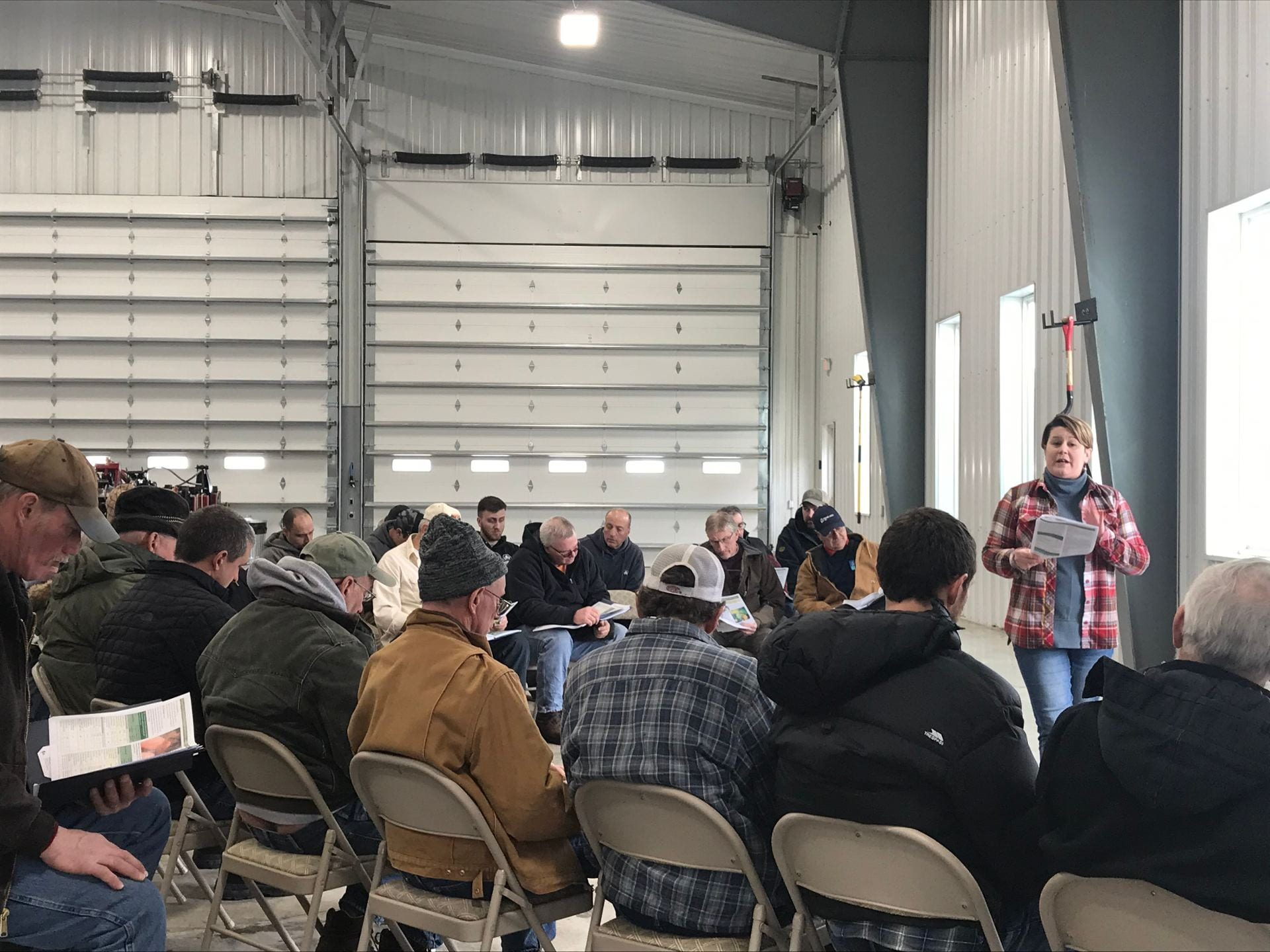 Photo shows Jaime Cummings speaking to a group of seated farmers inside a large, bright metal barn.
