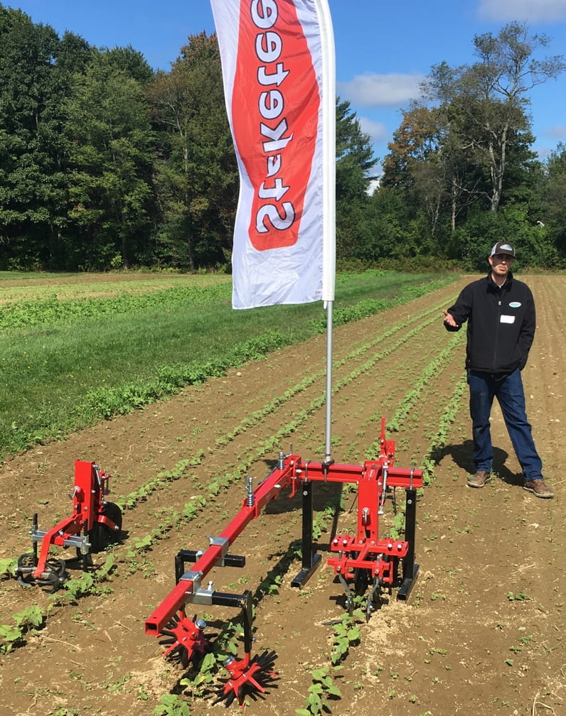 Image shows a sales rep from Steketee company, standing next to a pull behind cultivator that uses a multi-faceted method of disturbing soil and uprooting weeds
