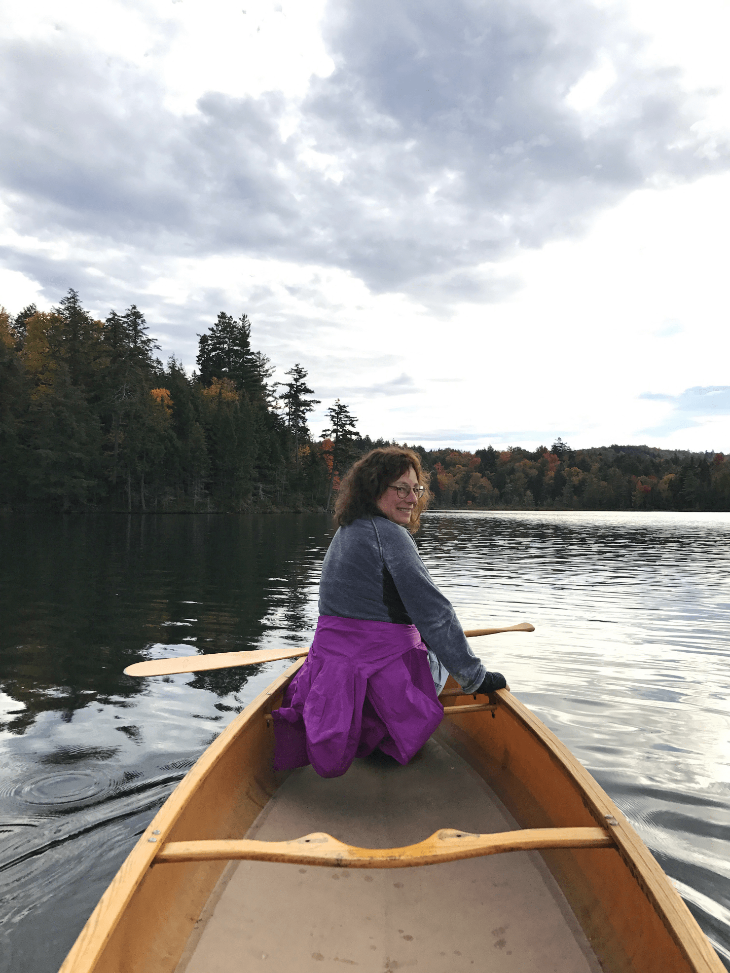 photo of Karen English in the front of a canoe on a lake in the Adirondack Mountains.