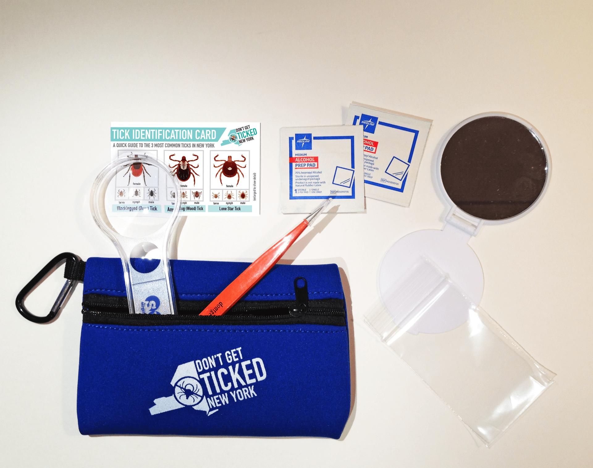 photo shows items inside a tick kit: magnifier, pointy tweezers, tick identification card, alchol swabs, small mirror for checking hard to see places, small zip loc bag to place tick in if found. All parts of a tick kit that is a small zippered pouch to keep handy when going outside.