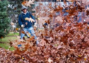 image of a man in long pants and sleeves, a baseball cap, and ear coverings using a leaf blower. In front of himn leaves are being blown towards the camera.
