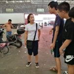 students talk to a buyer at a vegetable market