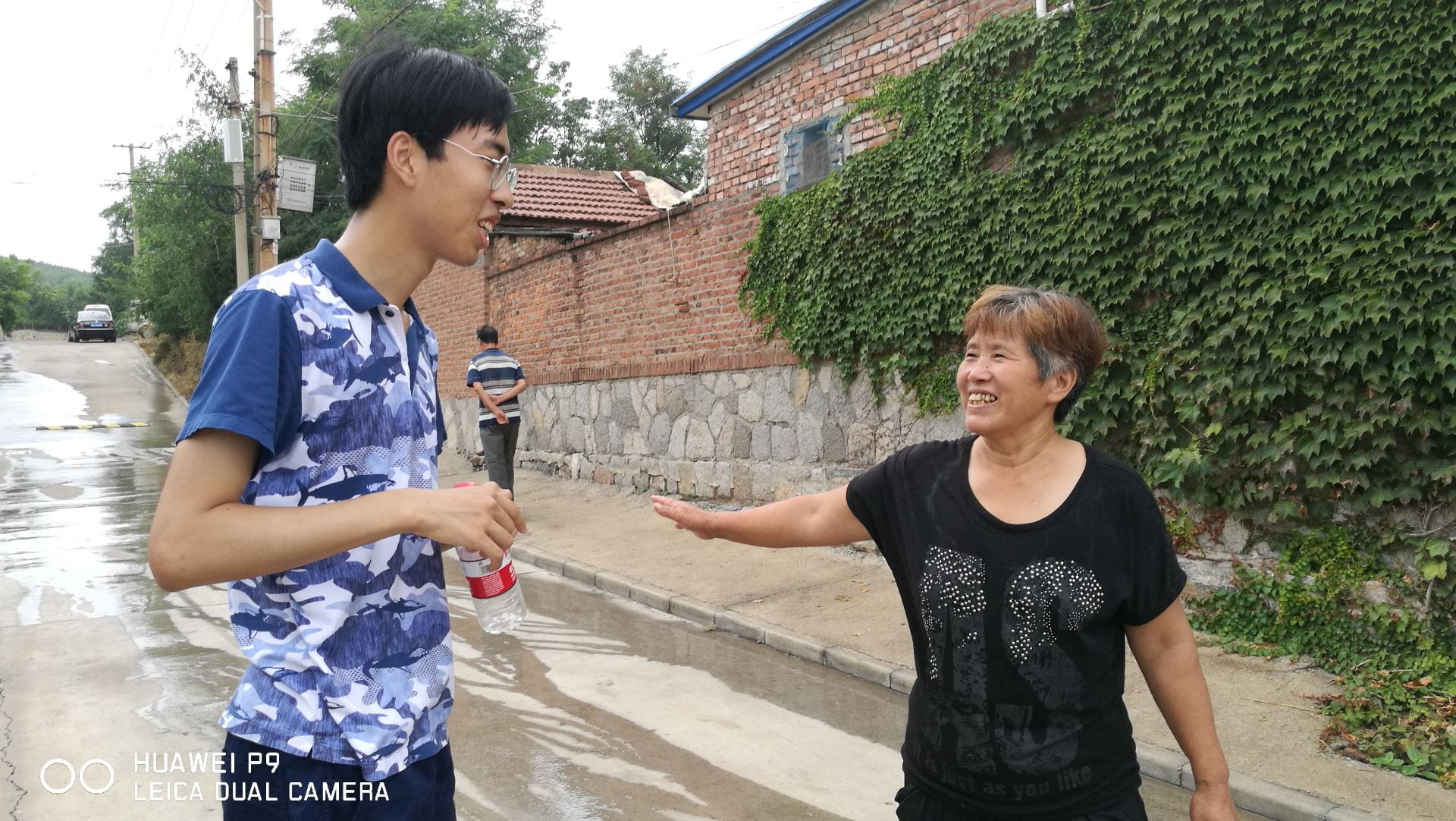 student talks to a resident of a village on the street