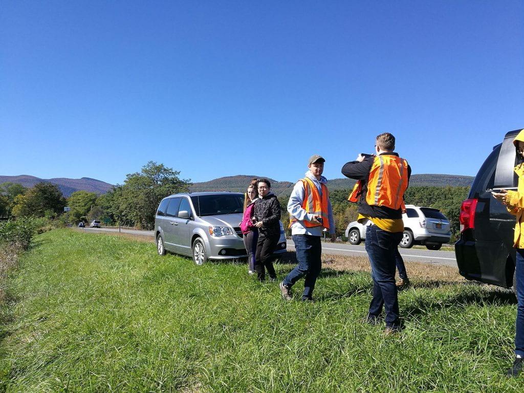 People wearing orange safety vests on a highway shoulder taking photos of surrounding hillsides