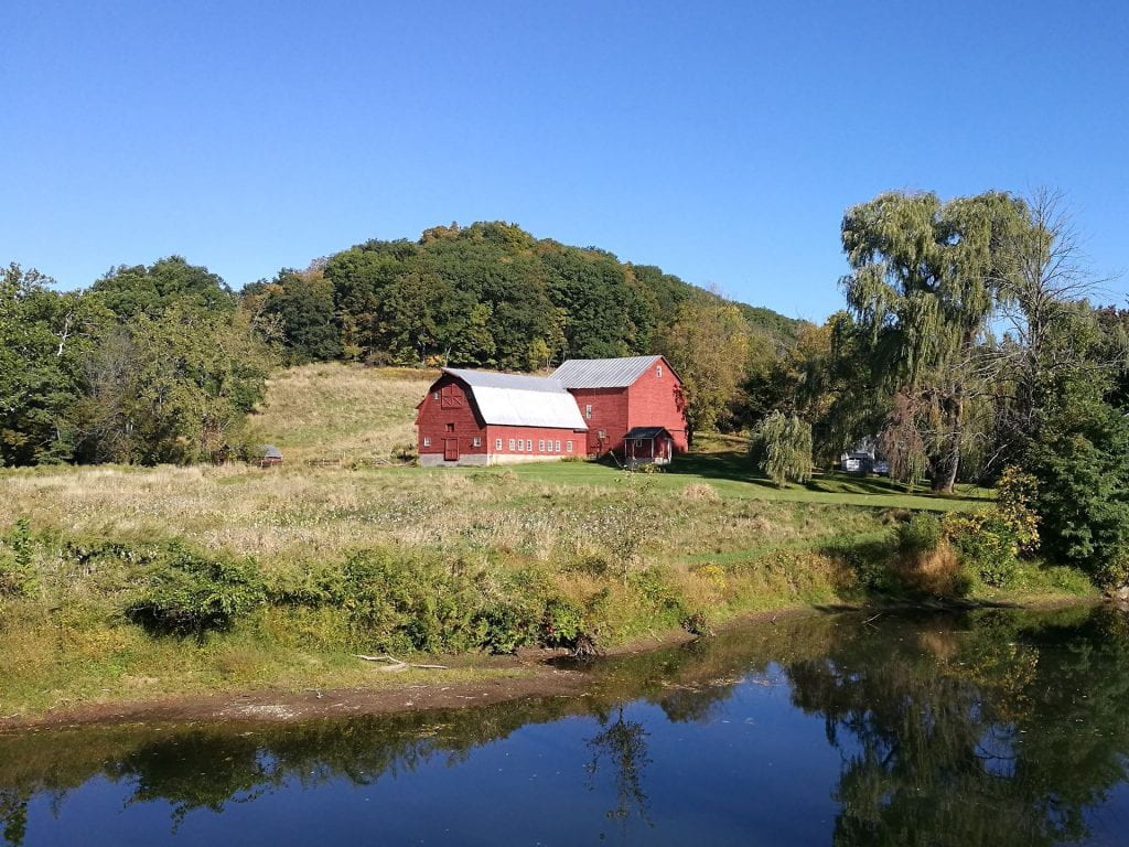 red barn near a body of water, immediately backed by a hill