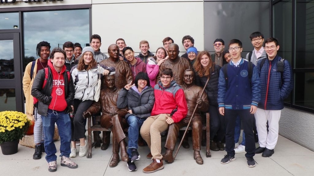 group of people posing with a statue