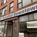 "Building emblazoned with a ""No Hospital Downtown"" sign"