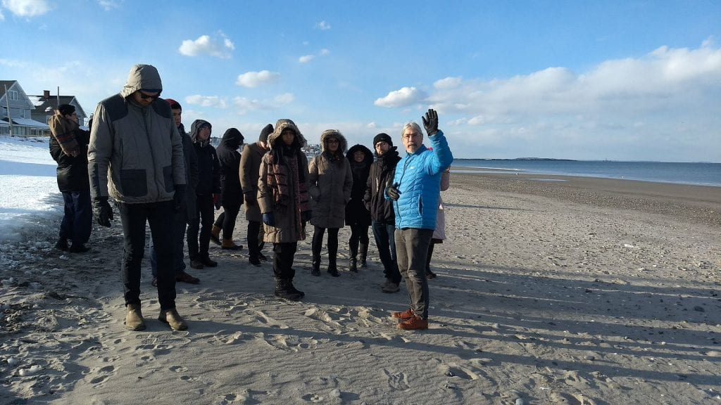 group of people in winter coats touring a beach