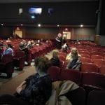 audience member speaking into microphone in auditorium