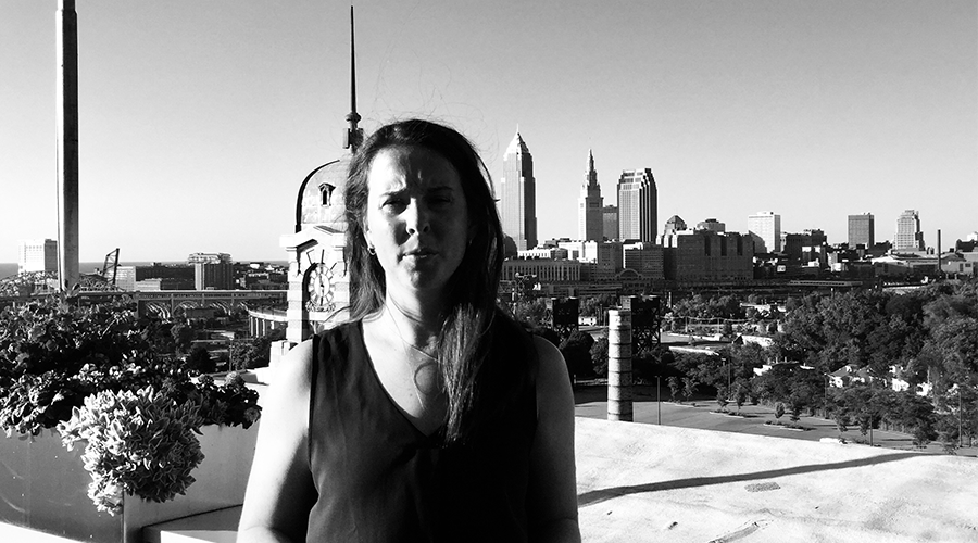 grayscale photo of woman with city skyline in background
